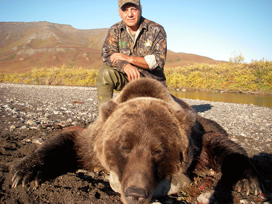 Grizzly bear hunter with his large bear.